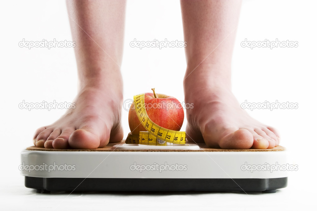 A pair of female feet standing on a bathroom scale with an apple and tape measure between them. — Stock Photo #5679183