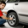 Male Changing Tire - Stock Photo