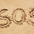 S.O.S written in the sand of an island with the ocean in the distance — Stock Photo #5693505