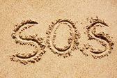 S.O.S written in the sand of an island with the ocean in the distance — Stock Photo