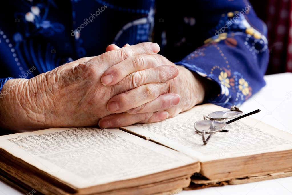 An old pair of hands in prayer on a book — Stock Photo #5692355