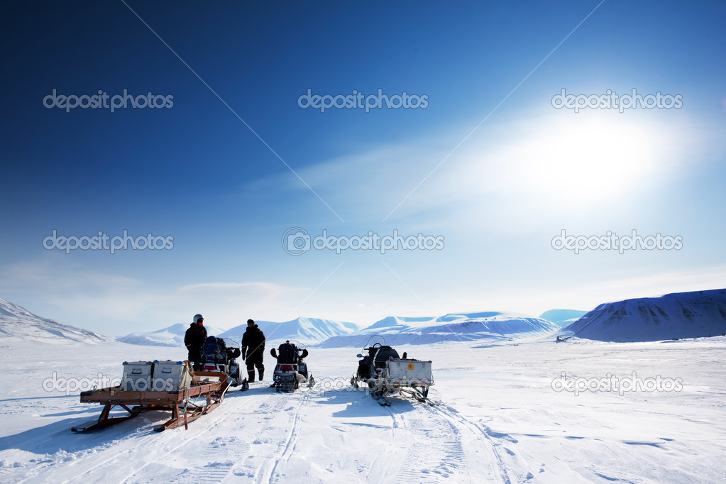 A group on a winter snowmobile adventure over a barren winter landscape  Stock Photo #5692408