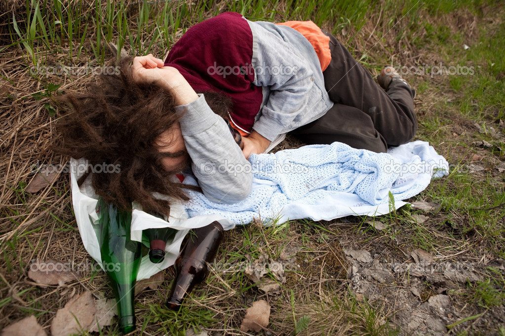 A drunk passed out in the ditch with a bunch of alcohol bottles — Stock Photo #5692928