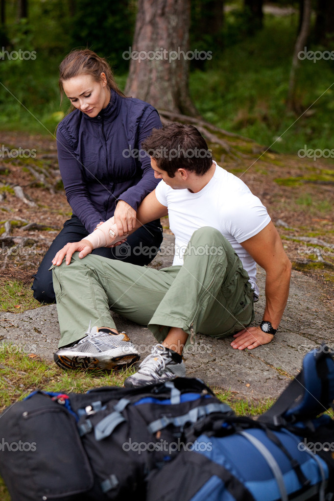 A woman applying an arm bandage on a male camper - focus on male face — Stock Photo #5695535