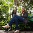 Young females talking to each other in park — Stock Photo