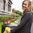 Stock Photo: Woman putting plastic waste in garbage bin