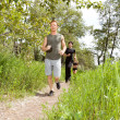 Stock Photo: Friends exercising in forest track