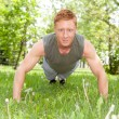 Man doing a push up in park - Stock Photo