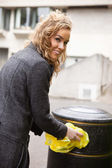 Happy woman putting plastic waste in garbage bin — Stock Photo