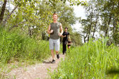 Friends exercising in forest track — Stockfoto