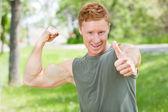 Homem flexionando e mostrando sinal de polegar para cima — Fotografia Stock
