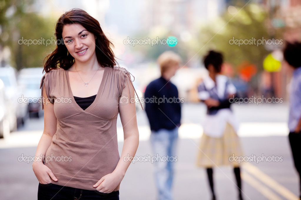A woman in a city setting with friends in the background — Stock Photo #5701868
