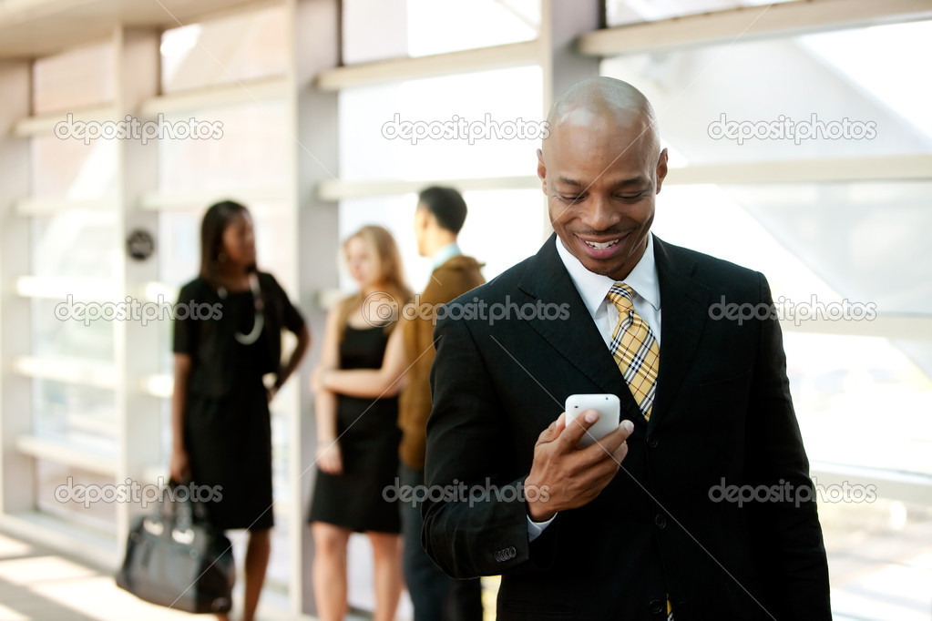 A business man with a smart phone and co-workers in the background — Stock Photo #5701906