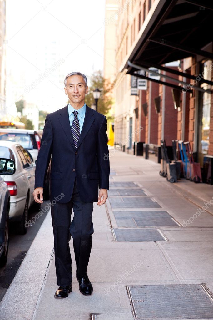 An asian looking business man walking in a street  Stock Photo #5702053