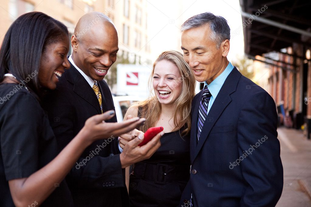 A group of business looking at a cell phone and laughing — Stock Photo #5702159