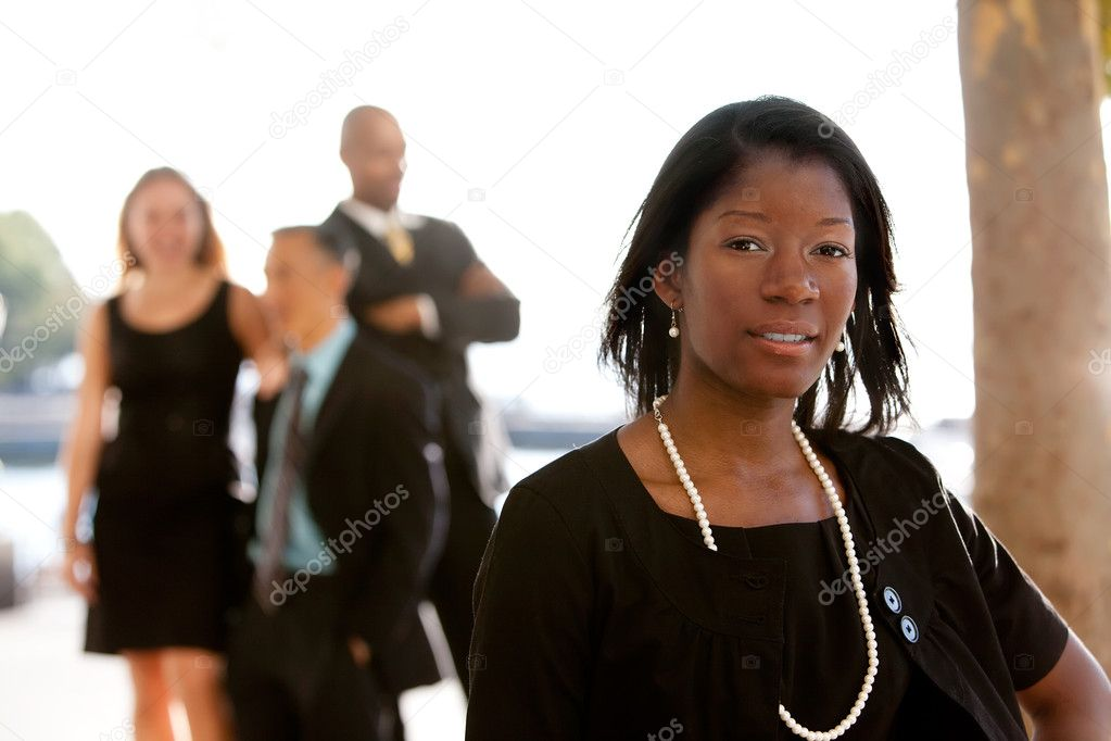 An attractive African American business woman with colleagues in the background — Zdjęcie stockowe #5702692