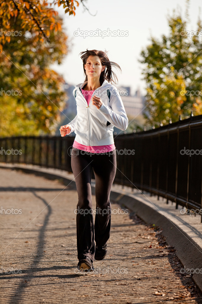 A young woman jogging in the park on a path — Stock Photo #5703053