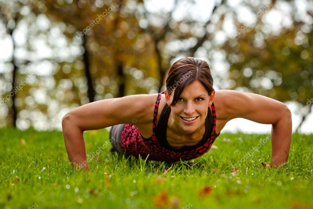 A caucasian female doing push ups in the park — Stock Photo #5703188