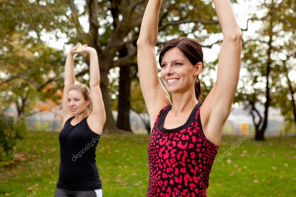 Two women stretching in a park - outdoor exercise — Stok fotoğraf #5703242