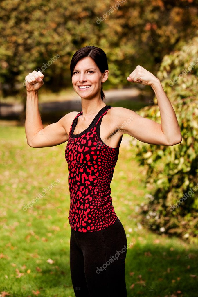A portrait of a woman flexing her bicep muscles — Stock Photo #5703375