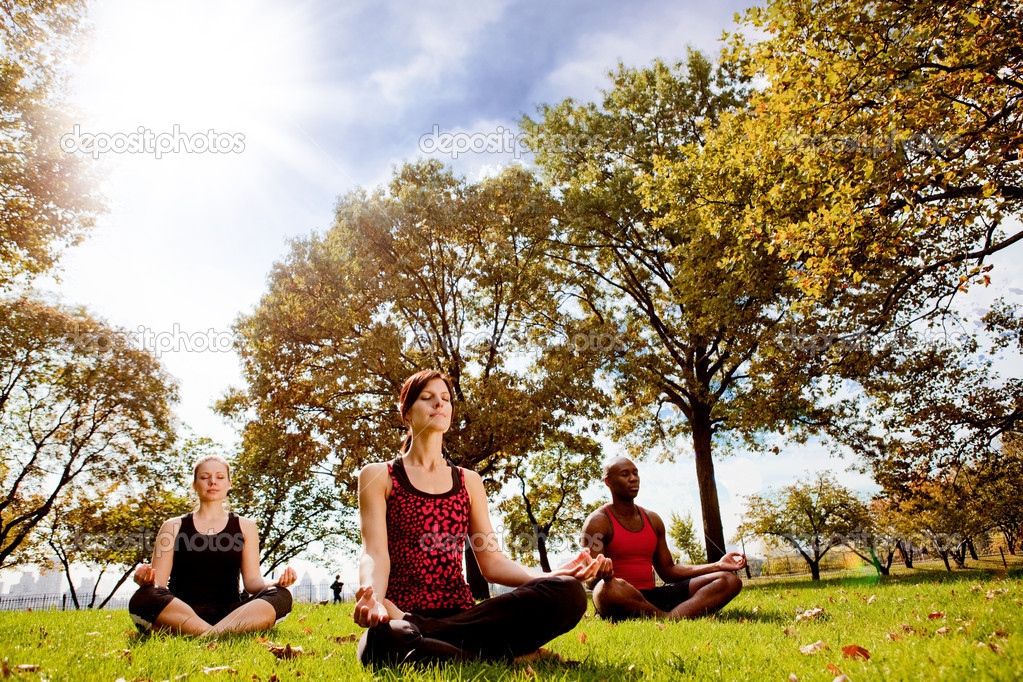 A group of doing yoga in a city park — Stock Photo #5703469