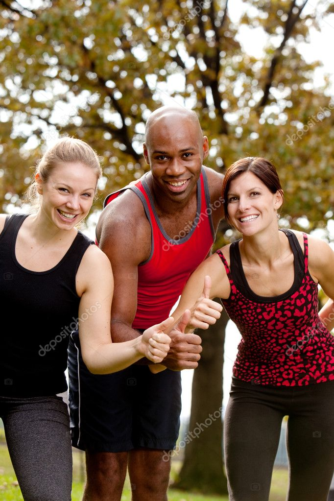 A group of exercising in the park, giving a thumbs up to the camera — Stock Photo #5703531