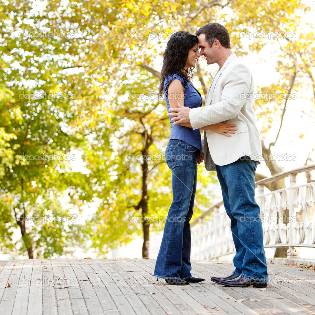 A happy couple in the park looking at the camera and hugging — Stok fotoğraf #5703870
