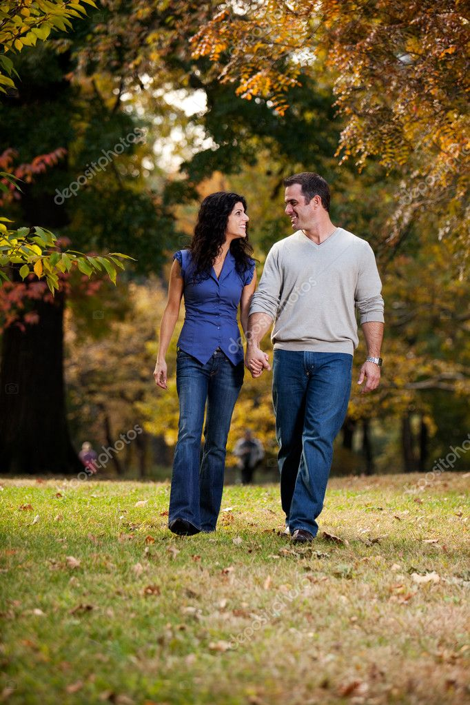 A happy couple walking in the park on grass  Stock Photo #5705159