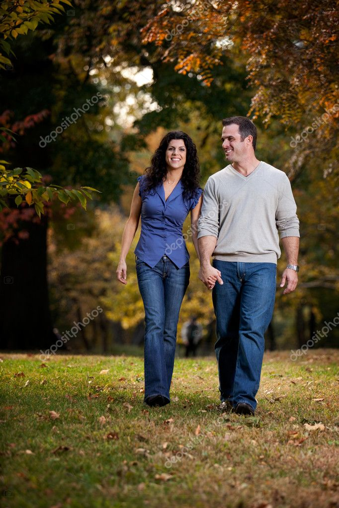 A happy couple walking in the park on grass — Stock Photo #5705179