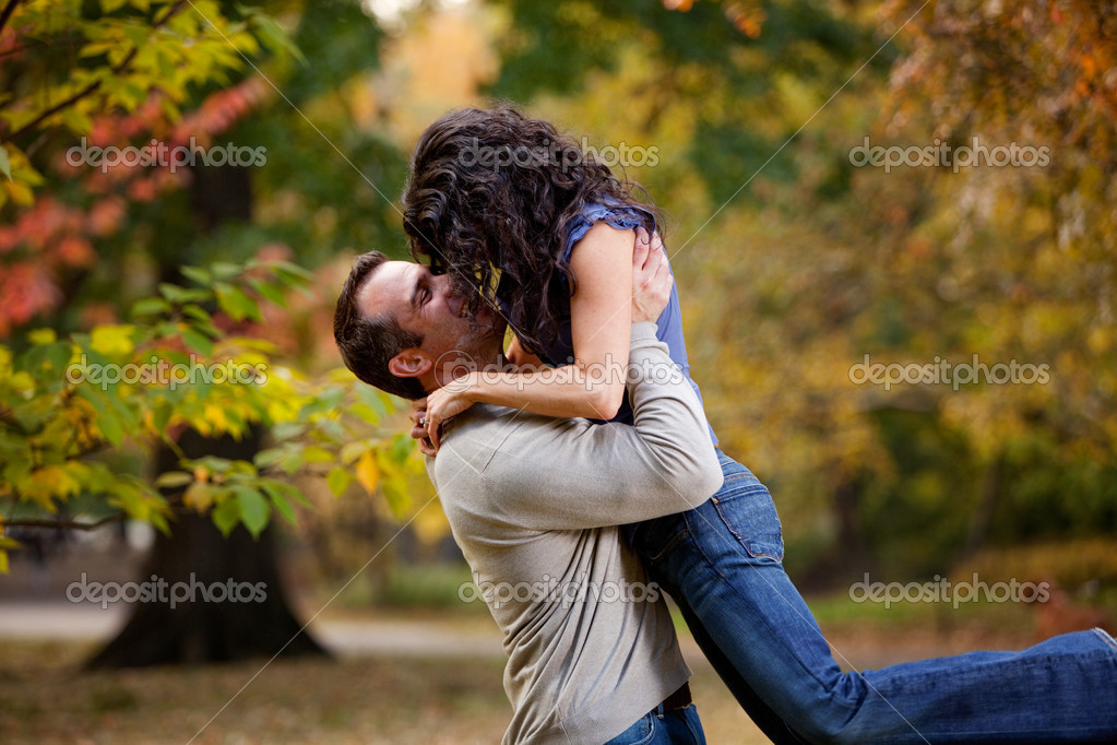 A man giving a woman a big hug in a park    #5705256