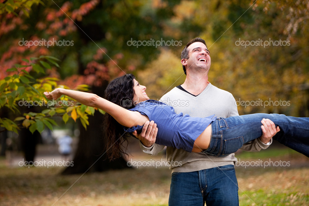 A playful couple - man holding woman in the park — Stock Photo #5705291