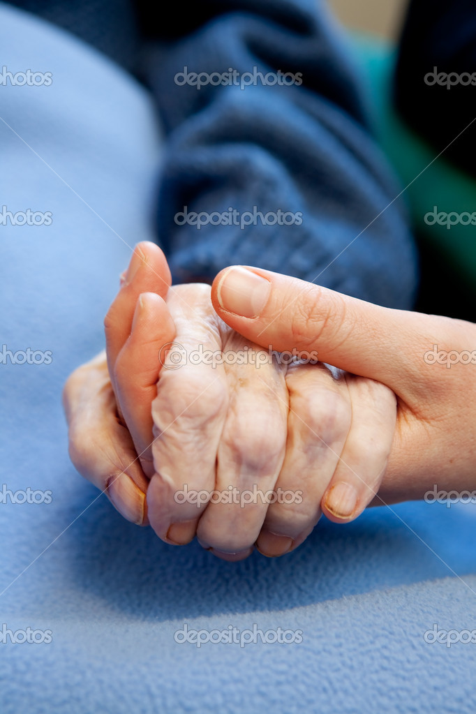 A young hand touches and holds an old wrinkled hand — Stock Photo #5705339