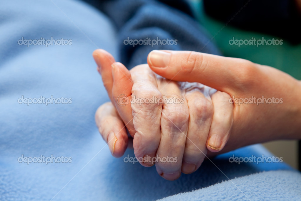 A young hand touches and holds an old wrinkled hand  Foto Stock #5705346