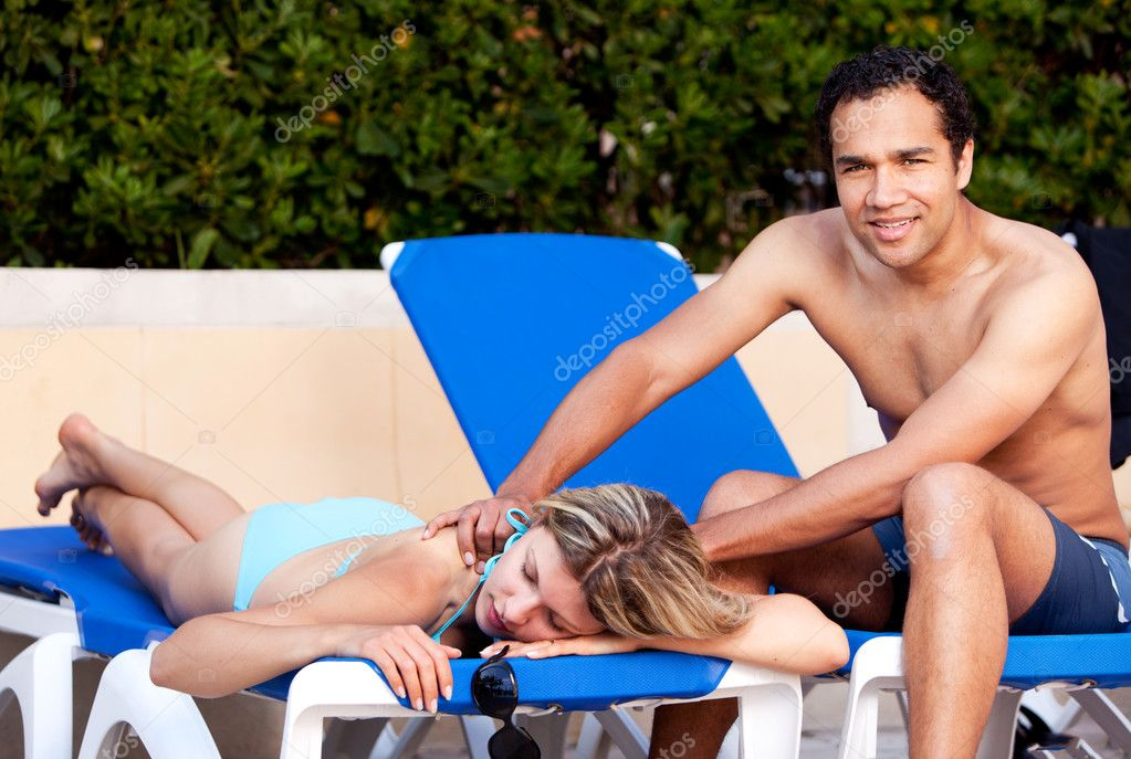 A couple relaxing by the pool, the man giving the woman a back massage — Stock Photo #5706905