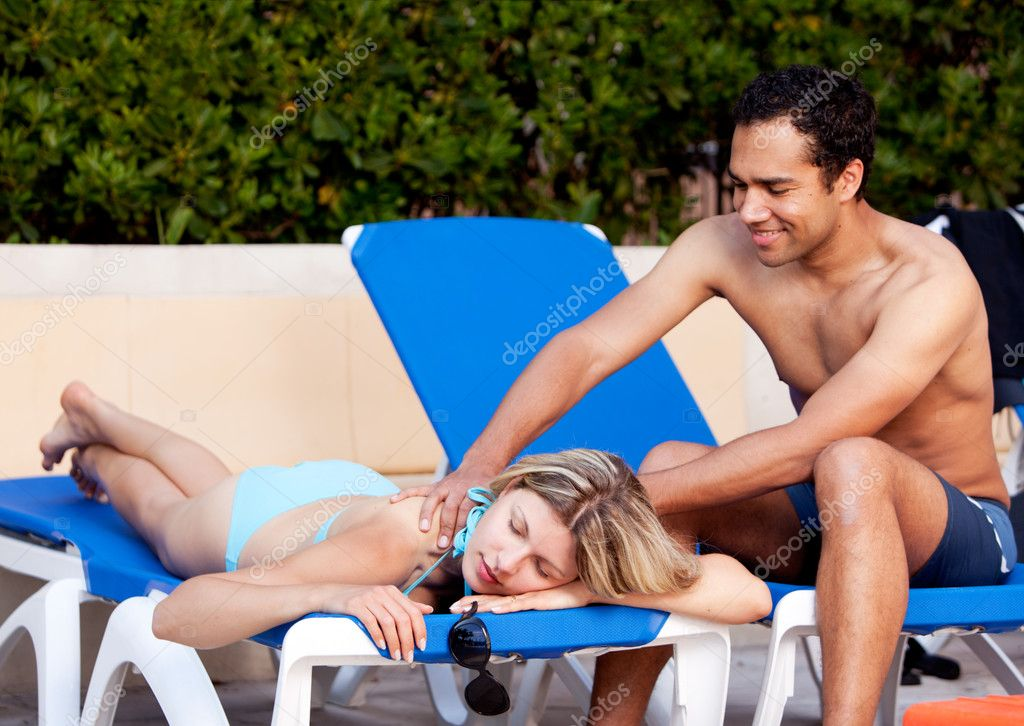 A woman receiving a back massage on a pool chair  Stock Photo #5706912