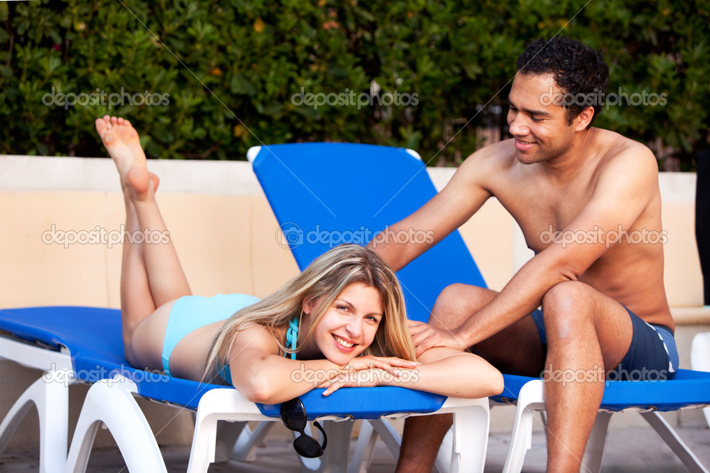 A man giving a back massage to a woman on a beach chair — Foto Stock #5706922