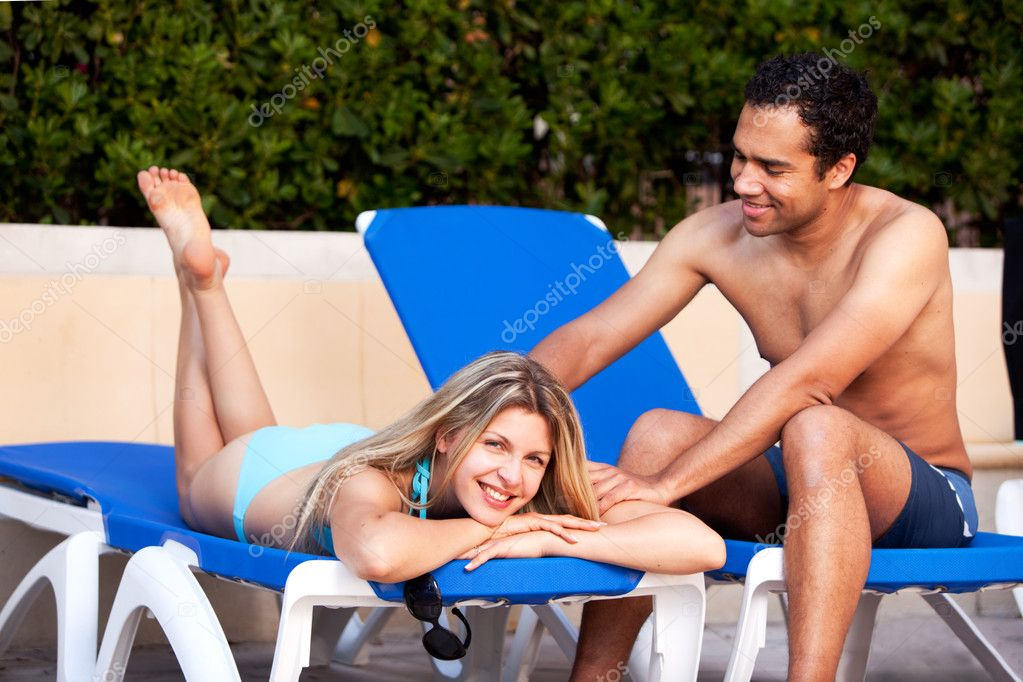A man giving a back massage to a woman on a beach chair — Stockfoto #5706922