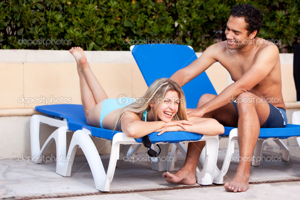 A happy couple relaxing beside a pool.  Stock Photo #5706927