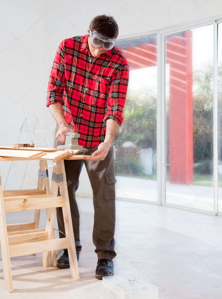 A man in a home interior sanding wood with an electric hand sander — Stock Photo #5707872