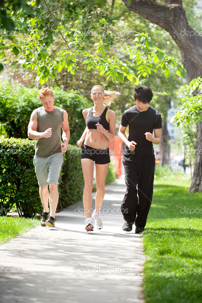 Three friends jogging in the park against blur background — Stock Photo #5708854