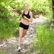 Woman smiling and running in forest — Stock Photo