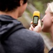 A couple outdoors in the forest using a GPS — Stock Photo #5710793