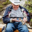 Elderly man playing with squirrel — Stock Photo #5710867