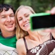 Young cheerful couple photographing themselves — Stock Photo