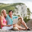 Relaxed couple with laptop while camping — Stock fotografie