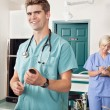 Stock Photo: Doctor with syringe while nurse taking down report