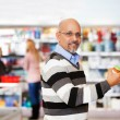 Smiling mature man shopping in the supermarket — Stok fotoğraf