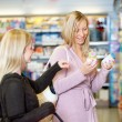 Young women smiling while shopping together — Stockfoto