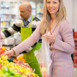 Portrait of a young woman buying fruits — Stockfoto