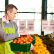 Market assistant holding box of tomatoes — Stock Photo